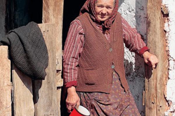Stara majka na pragu trošne kuće