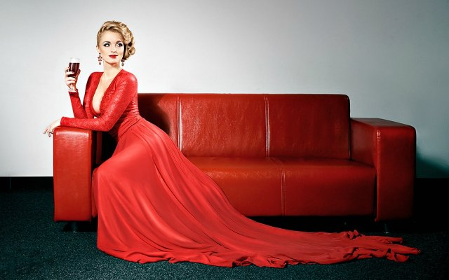 beautiful-woman-in-red-dress-seat-on-red-sofa