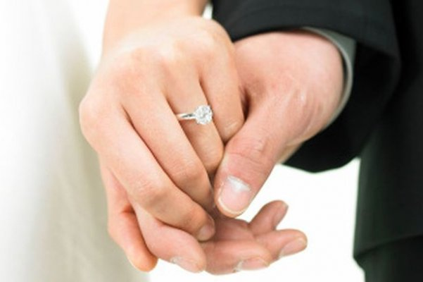 a-bride-wearing-a-wedding-ring-and-a-bridegroom-holding-her-hands